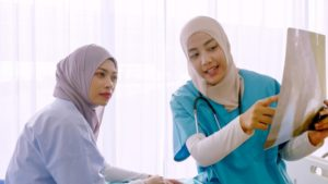 Muslim female doctor explaining chart to patient at hospital ro